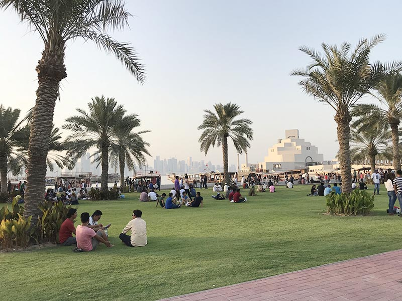 Migrant workers sitting at Dohau2019s waterfront in Qatar, August 18, 2018. Photo: Thomson Reuters Foundation