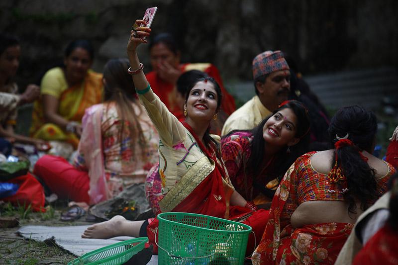 Nepali Hindu women take pictures while performing prayer rituals during Rishi Panchami festival on the banks of Bagmati River in Kathmandu, on Friday, September 14, 2018. Photo: Skanda Gautam
