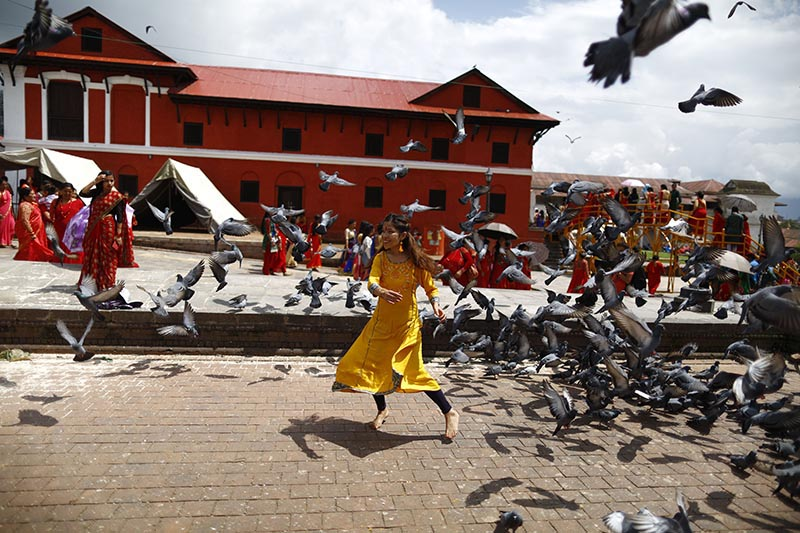 A woman plays with a bunch of pigeons during Teej festival on the premises of Pashupathinath Temple in Kathmandu, on Wednesday, September 12, 2018. Photo: Skanda Gautam