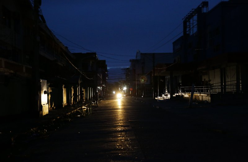 A motorcycle provides light along a dark street after electricity was shut-off following the onslaught of Typhoon Mangkhut in Tuguegarao city in Cagayan province, northeastern Philippines on Saturday, Sept. 15, 2018. Photo: AP