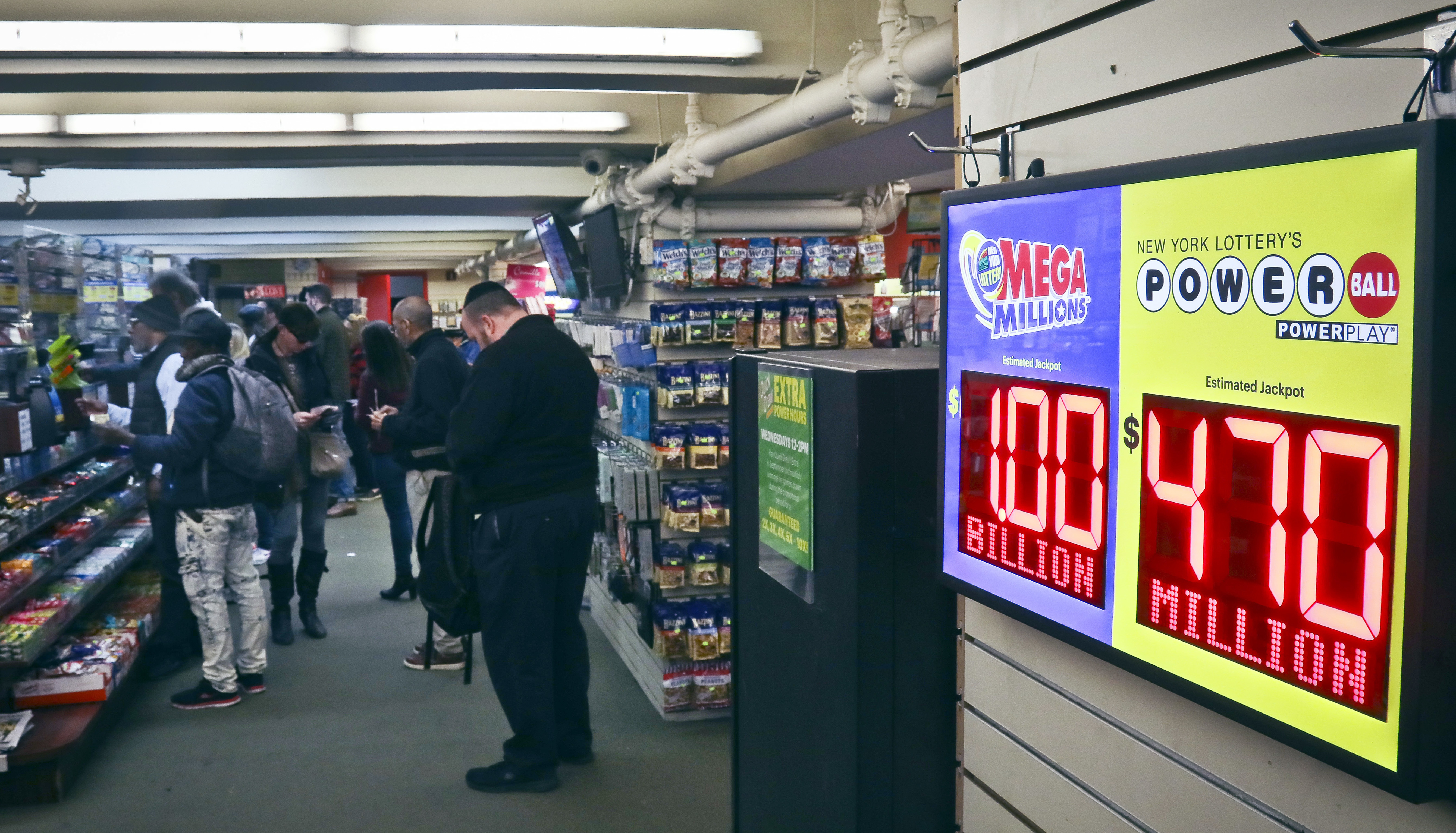Lottery players buy Mega Millions lottery tickets, Friday Oct. 19, 2018, in New York. The estimated jackpot for Friday's drawing has soared to $1 billion. AP Photo