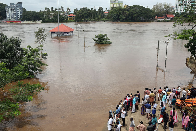 FILE PHOTO: People stand on the steps of Aluva Shiva Temple complex submerged in water after the opening of Idamalayar dam gate following heavy rains, on the outskirts of Kochi, India, August 9, 2018. Photo: Reuters