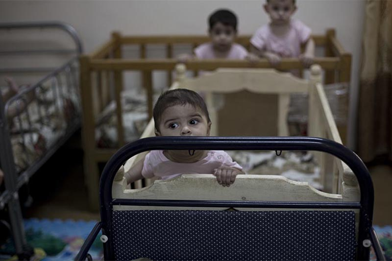 FILE -  Baby girls stand up in their cribs at Salhiya Orphanage, which now hosts foreign and Iraqi children of Islamic State militants, in Baghdad, Iraq, on August 15, 2018. The enslavement of Iraqi Yazidi women by the Islamic State group has left a heartbreaking legacy u2014  hundreds of children fathered by militants. While some of the women want nothing to do with babies born of rape and slavery, some want to keep them, but they face rejection by families traumatized by the militants who killed hundreds of Yazidis and tried to wipe out the community. Photo: AP