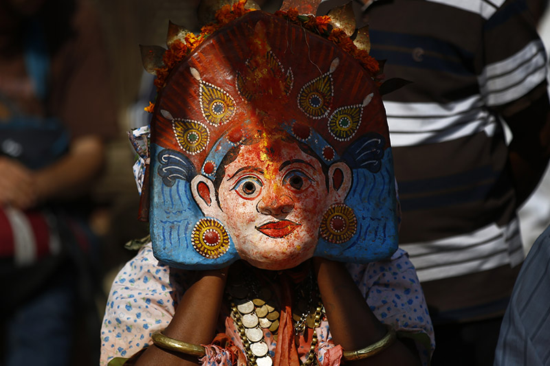 A masked person dressed as a deity arranges the mask ahead of the 'Nava Durga' dance during Kojagrat Purnima, the last day of Dashain festival, inside Patan Durbar Square premises, in Lalitpur, on Wednesday, October 24, 2018. Photo: Skanda Gautam/THT