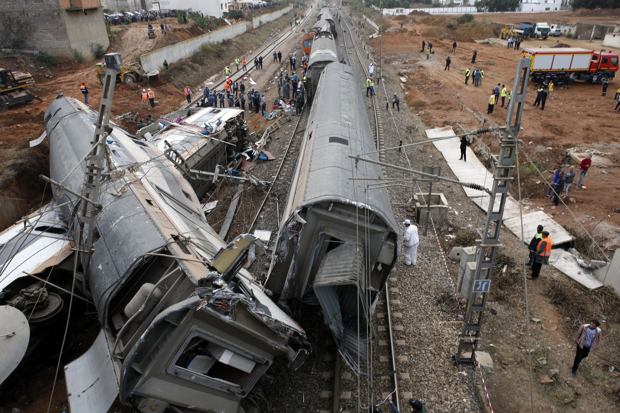 People gather after train derailed Tuesday Oct.16, 2018 near Sidi Bouknadel, Morocco. Photo: AP