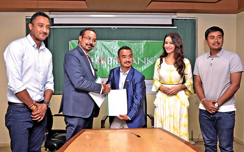 CEO of Nabil Bank Anil Keshary Shah shakes hands with Queens Events Management Pvt Ltd MD Chhumbi Lama (right) as national cricket team skipper Paras Khadka (extreme left), vice-captain Gyanendra Malla and Miss Nepal Shristi Shrestha look on during a signing ceremony of Pokhara Premier League in Kathmandu on Sunday. Photo: Naresh Shrestha/ THT