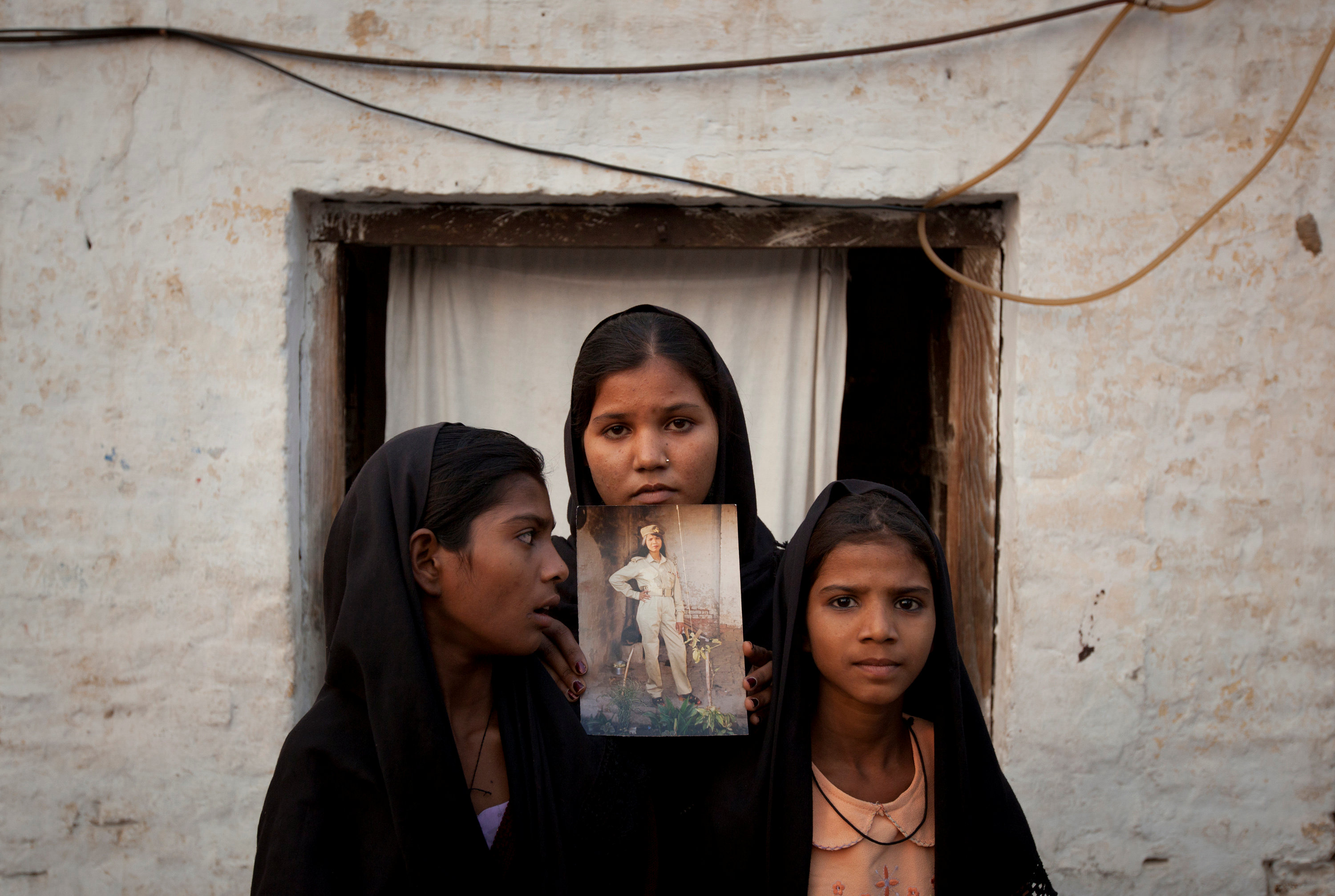 FILE PHOTO: The daughters of Pakistani Christian woman Asia Bibi pose with an image of their mother while standing outside their residence in Sheikhupura located in Pakistan's Punjab Province November 13, 2010. REUTERS