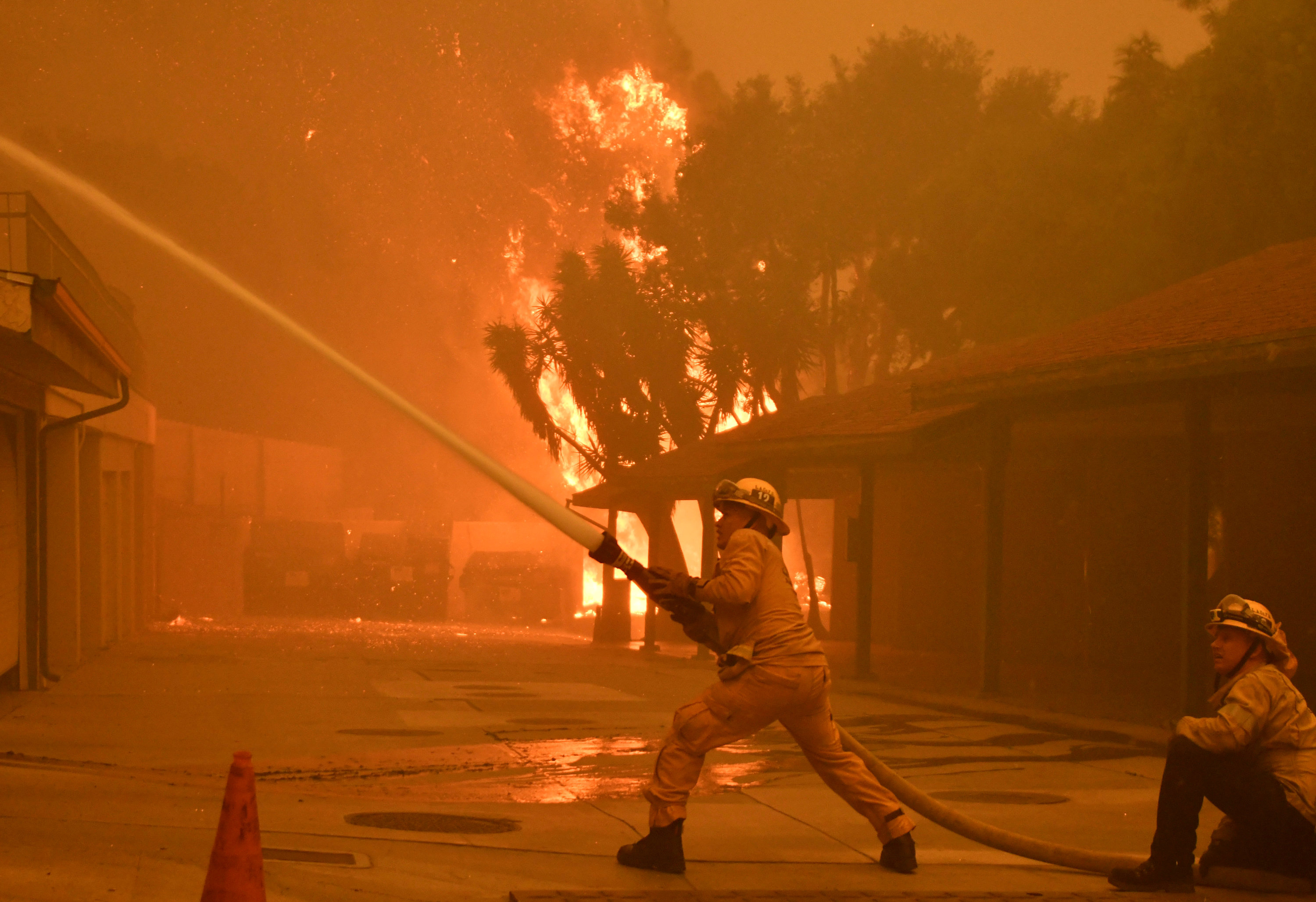 Firefighters hose down a condo unit during the Woolsey Fire in Malibu, California, US November 9, 2018.  REUTERS
