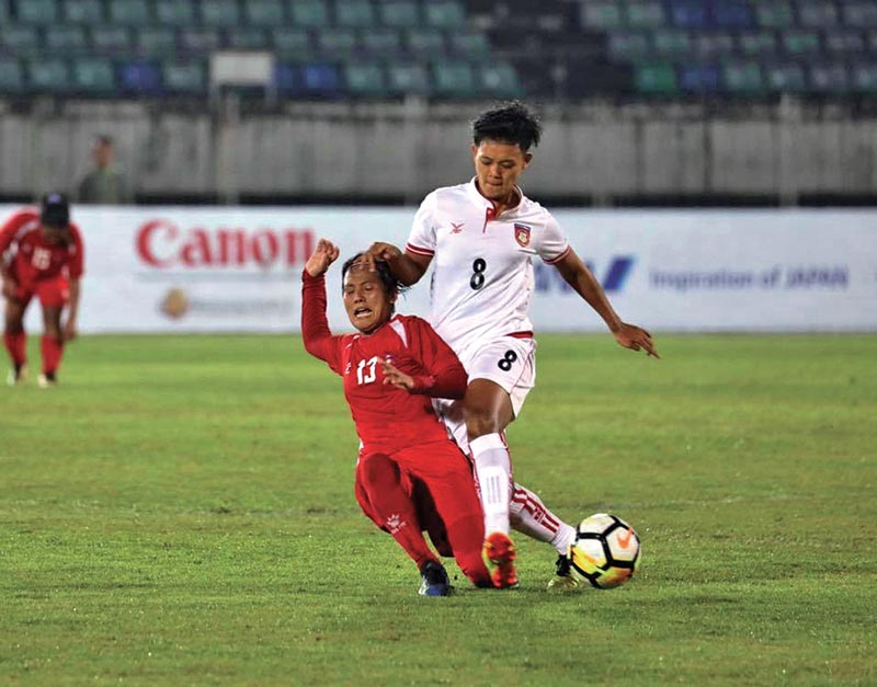 Nepal's Dipa Rai (left) and Myanmar's July Kyaw vie for the ball during their AFC Women's Olympic Qualifying Tournament match at the Thuwunna Football Stadium in Yangon on Sunday. Photo Courtesy: Myanmar Football Federation