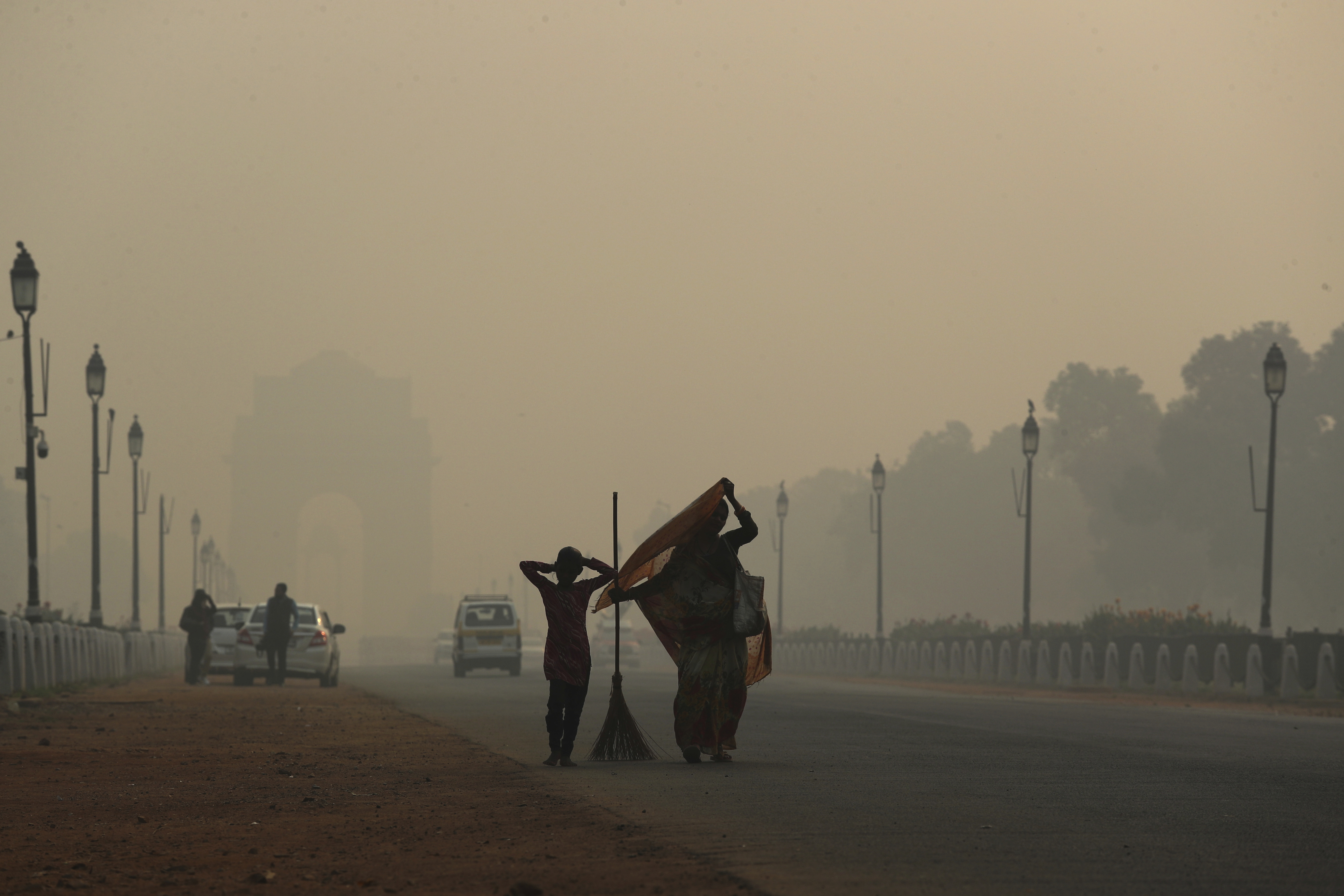 A municipal worker with her daughter leaves after sweeping the India Gate area as a thick lawyer of pollution haze hangs a day after Diwali festival, in New Delhi, India, Thursday, Nov. 8, 2018. Toxic smog shrouds the Indian capital as air quality falls to hazardous levels with tens of thousands of people setting off massive firecrackers to celebrate the major Hindu festival of Diwali on Wednesday night. Photo: AP