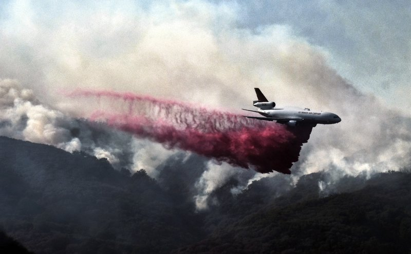 A firefighting DC-10 makes a fire retardant drop over a wildfire in the mountains near Malibu Canyon Road. Photo: AP