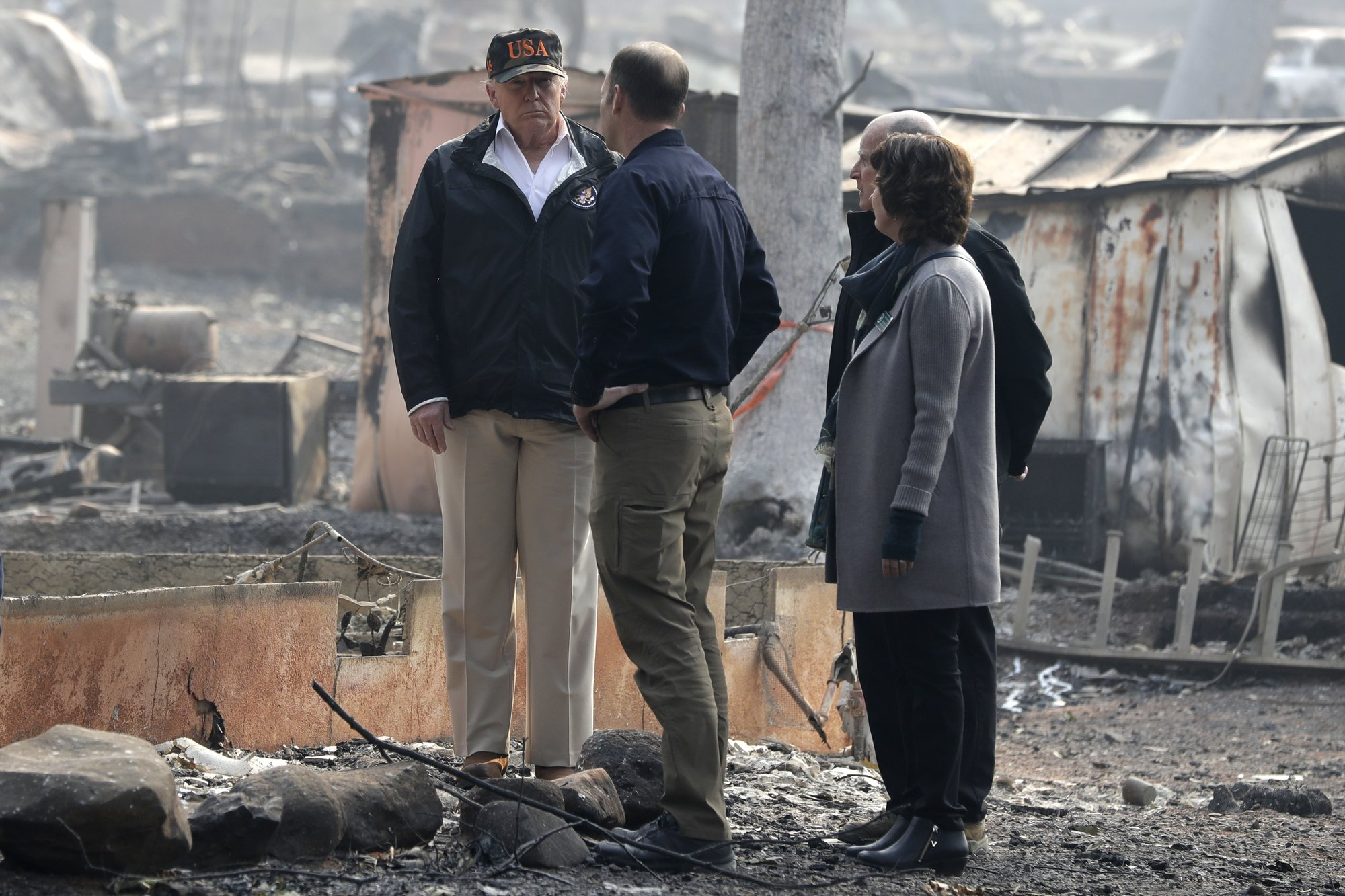 President Donald Trump talks to FEMA Administrator Brock Long as he tours Paradise, Calif., California Gov. Jerry Brown and Paradise Mayor Jody Jones during a visit to a neighborhood impacted by the wildfires, on Saturday, Nov. 17, 2018. Photo: AP
