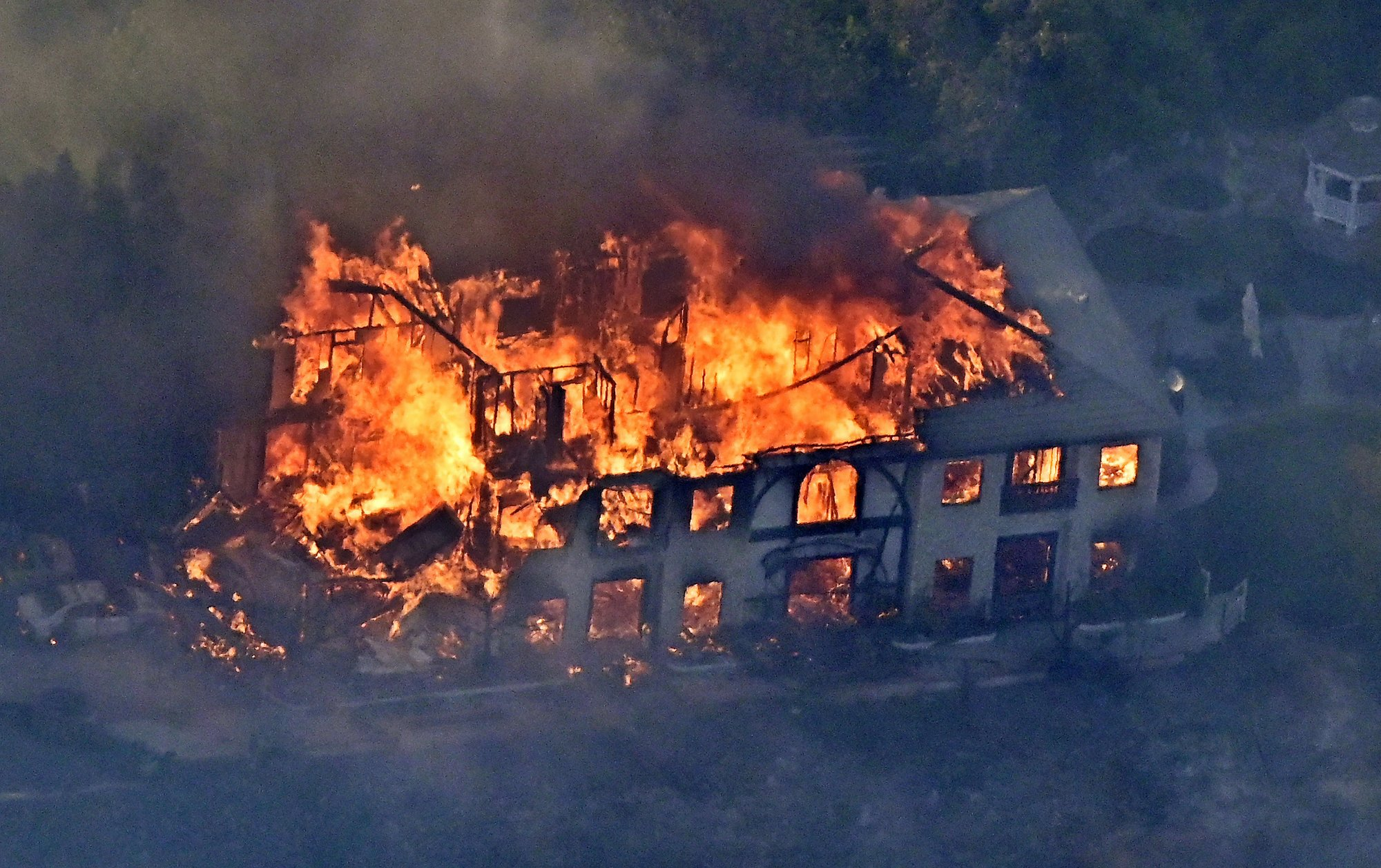 A home burns Friday, Nov. 9, 2018, as seen from a helicopter in the Calabasas section of Los Angeles. Photo: AP