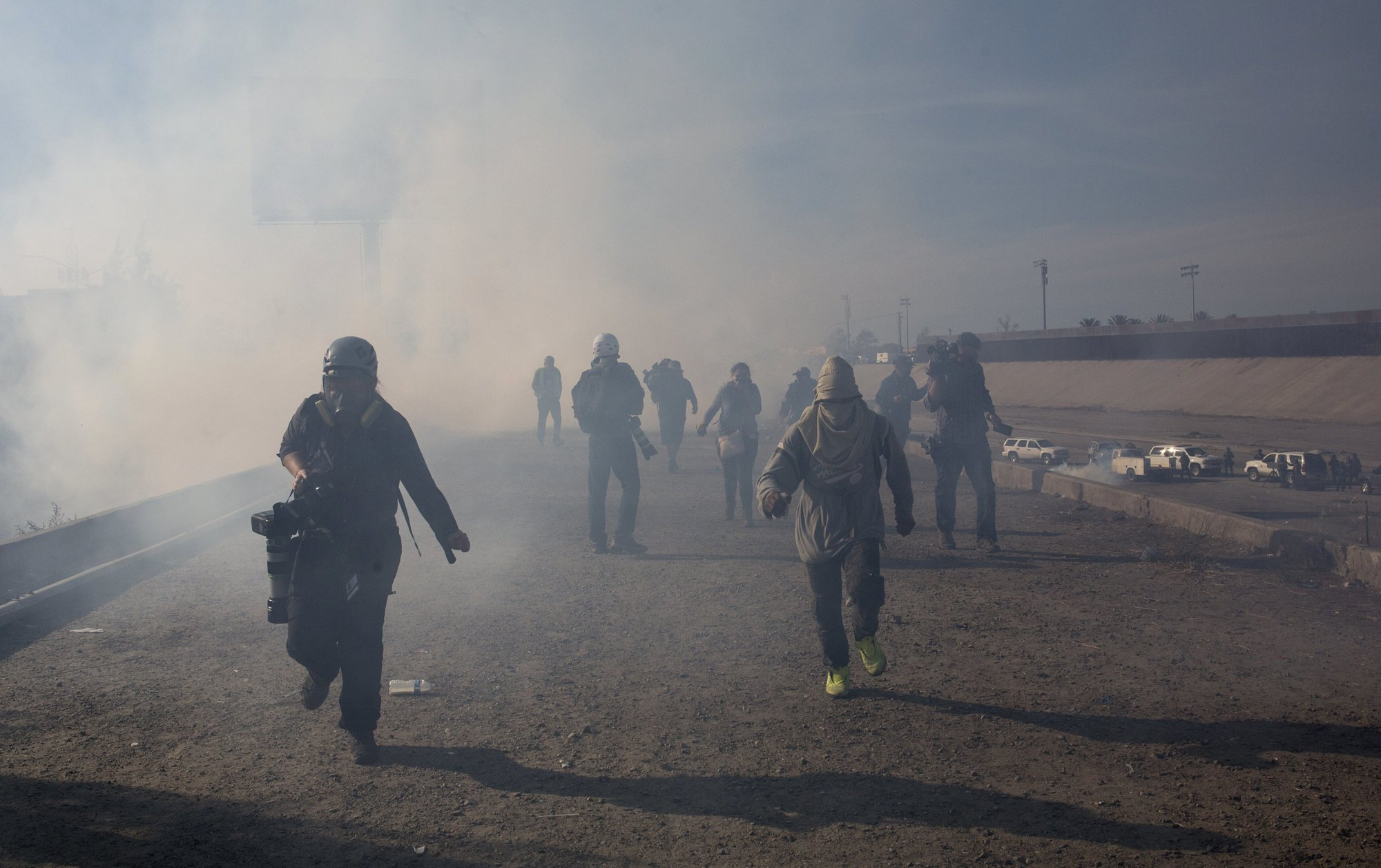 Migrants run from tear gas launched by U.S. agents, amid photojournalists covering the Mexico-U.S. border, after a group of migrants got past Mexican police at the Chaparral crossing in Tijuana, Mexico, on Sunday, Nov. 25, 2018. Photo: AP