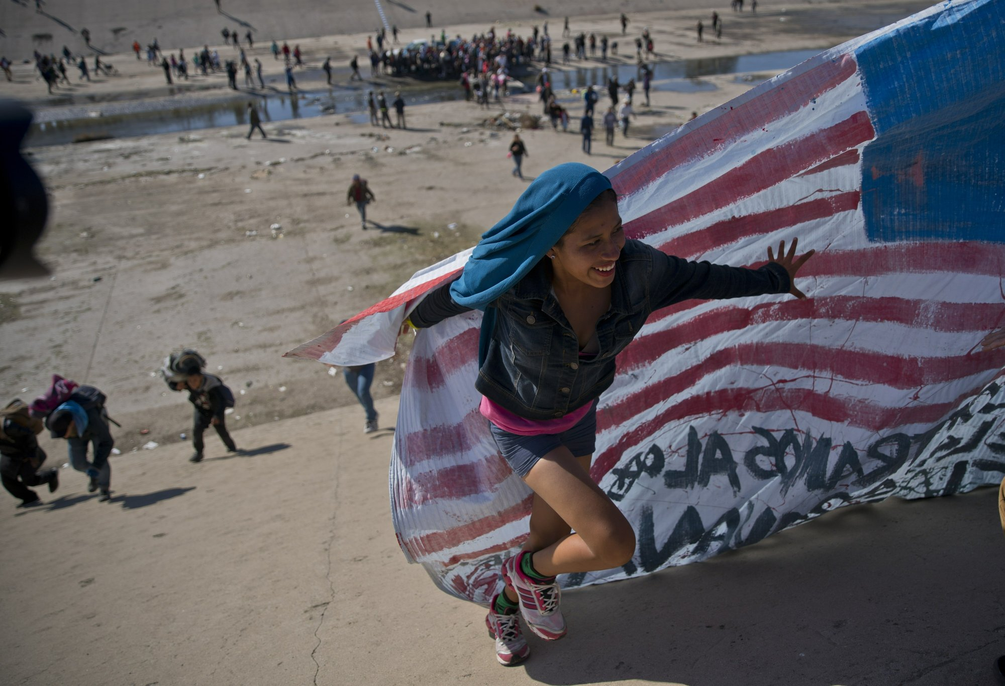 A migrant woman helps carry a handmade US flag up the riverbank at the Mexico-U.S. border after getting past Mexican police at the Chaparral border crossing in Tijuana, Mexico, Sunday, Nov. 25, 2018, as a group of migrants tries to reach the US. Photo: AP