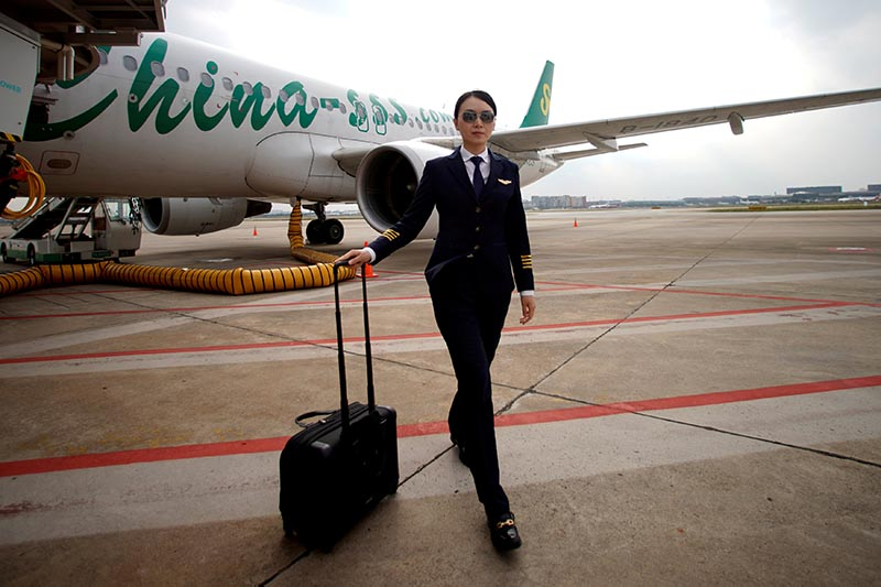 Captain Han Siyuan, 30, poses with Spring Airlines' Airbus A320 after landing at Hongqiao International Airport in Shanghai, China October 18, 2018. Photo: Reuters