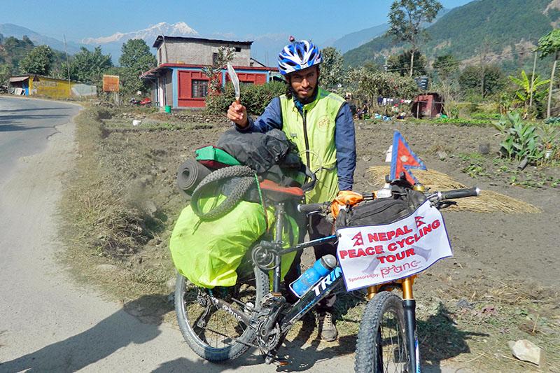 A 22-year-old Tej Prasad Parajuli, Jhapa native, brandishes Bhojpure Khukuri in Lamjung, on Tuesday, November 27, 2018. Parajuli is on a nation-wide cycle tour to promote traditional Bhojpure Khukuri. Photo: Ramji Rana