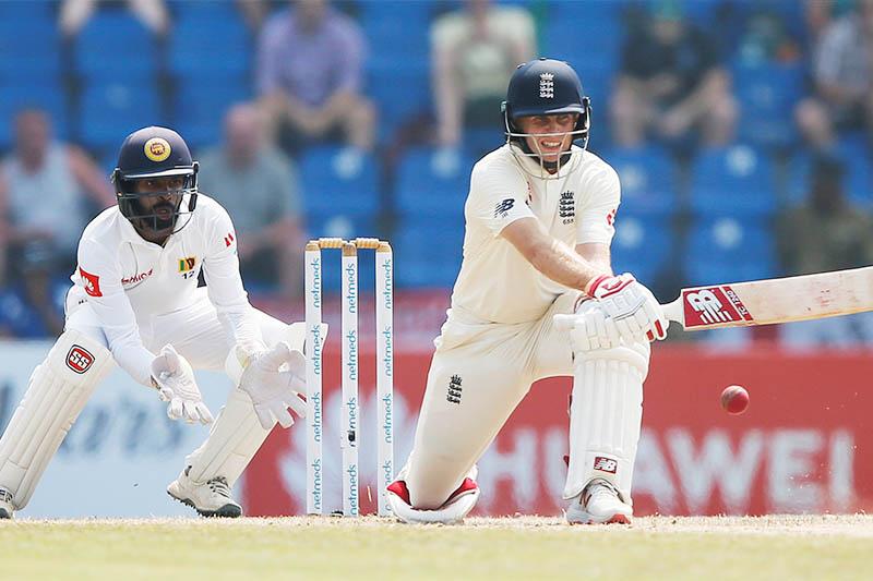 England's captain Joe Root (R) plays a shot next to Sri Lanka's wicketkeeper Niroshan Dickwella. Photo: Reuters