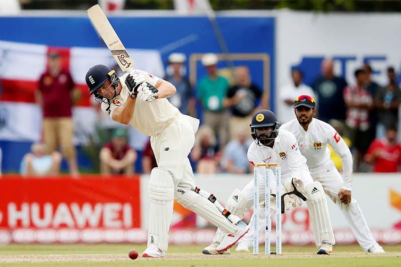 England's Jos Buttler (L) plays a shot next to Sri Lanka's wicketkeeper Niroshan Dickwella. Photo: Reuters