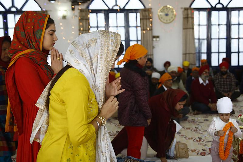Women and men from the Sikh community offer prayers during Guru Nanak Jayanti, a Sikh festival that marks the 549th birth anniversary of Guru Nanak, at Gurudwara in Lalitpur, on Friday, November 23, 2018. Photo: Skanda Gautam/THT