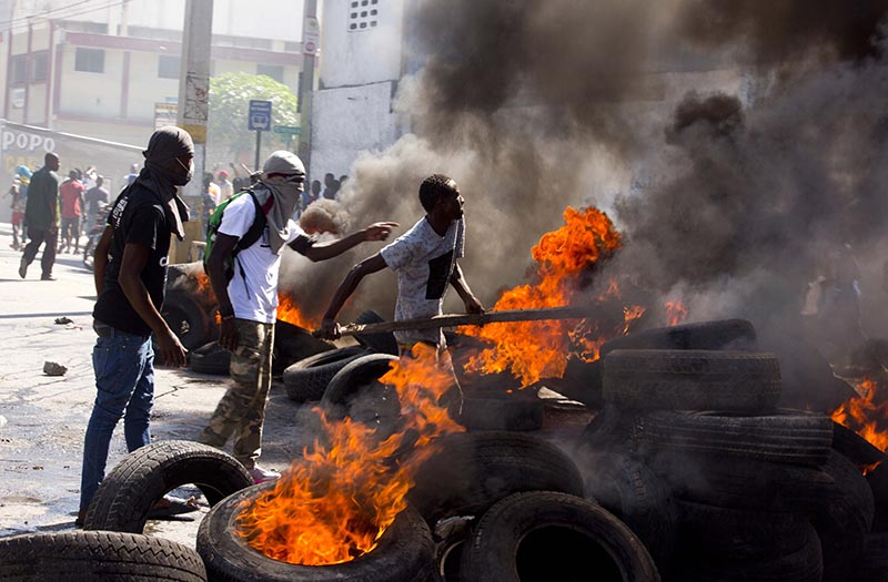 Men burn block a road with burning tires during an opposition protest demanding to know how Petro Caribe funds have been used by the current and past administrations, on the sidelines of events marking the 215th anniversary of independence Battle of Vertieres in Port-au-Prince, Haiti, Sunday, Nov. 18, 2018. Photo: AP Photo/Dieu Nalio Chery