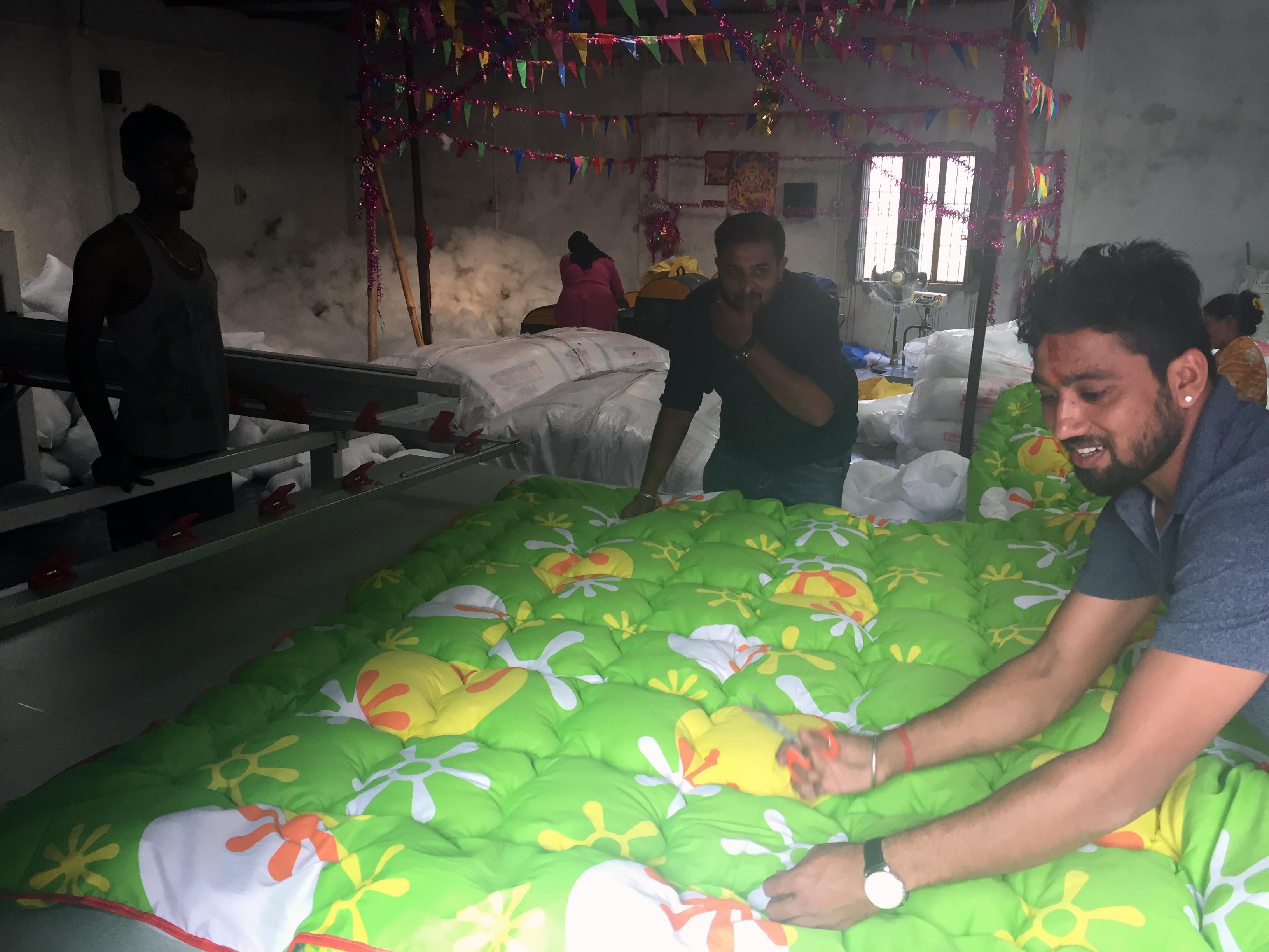 Manish Bhagat (Left) and Shreeyans Jain (Centre) inspect and add finishing touches to a fibre blanket produced at their factory in Biratnagar while their factory assistant Roshan Paswan watches on November 19, 2018. Photo: Prahlad Rijal/THT
