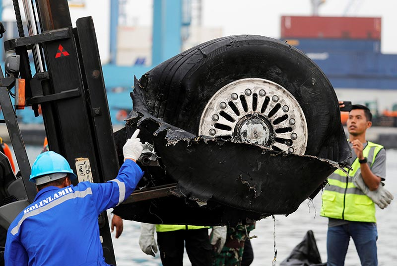 A worker assists his colleague during the lift up of a damaged tyre from Indonesian forensic policemen stand beside a damaged tyre from the the Lion Air flight JT610 jet, at Tanjung Priok port in Jakarta, Indonesia, November 5, 2018. Photo: Reuters