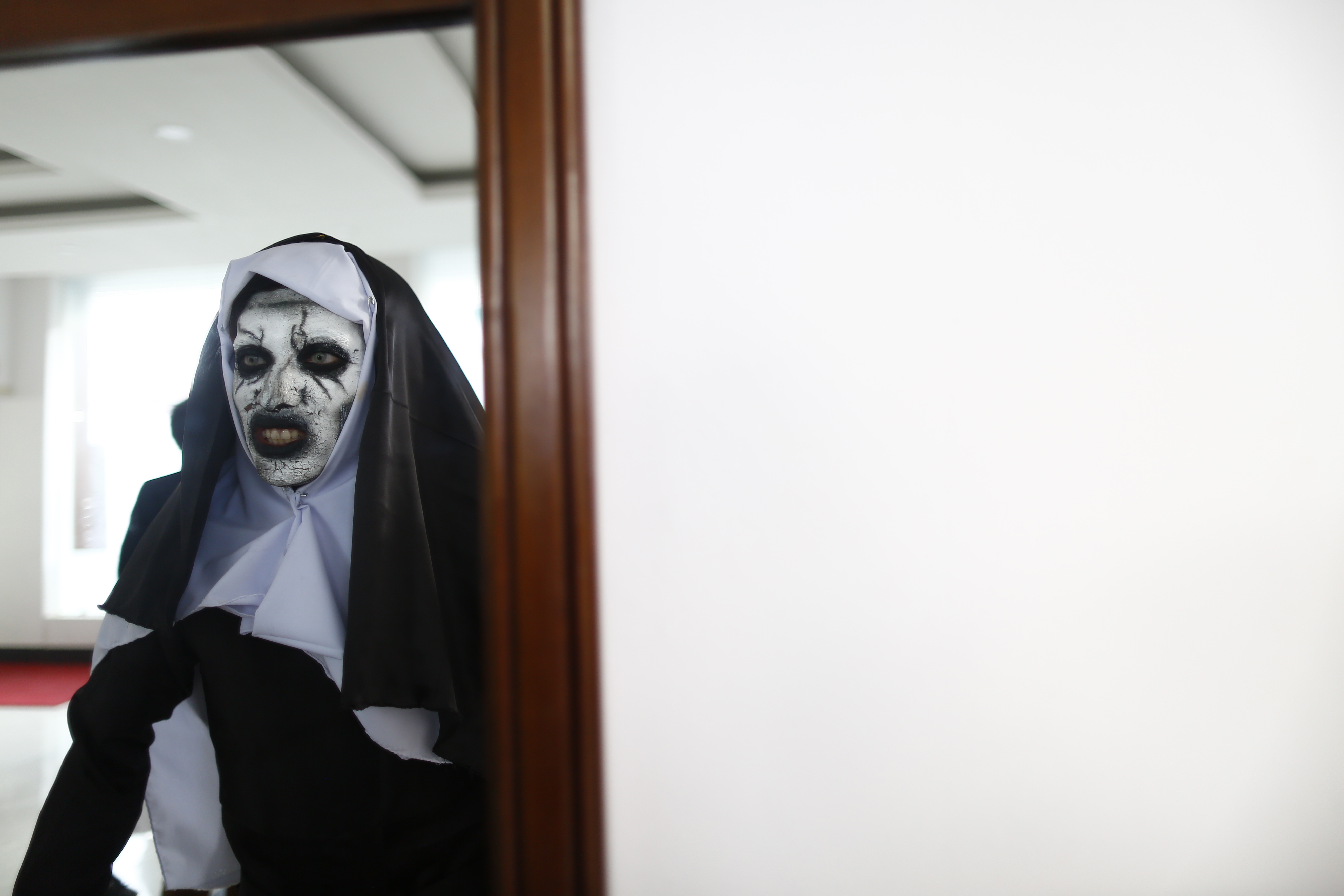 A person dressed in an attire of a ghost-nun looks at a mirror during Com Cos Con in Lalitpur, on Saturday, November 03, 2018. Photo: Skanda Gautam/THT