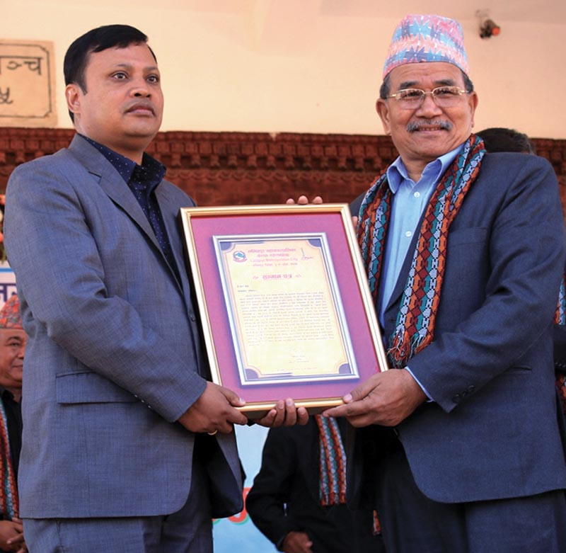 Mayor of Lalitpur Metropolitan City Chiri Babu Maharjan (right) handing over a letter of felicitation to President of Three Star Club Arun Man Joshiu00a0 in Lalitpur on Saturday. Photo: THT