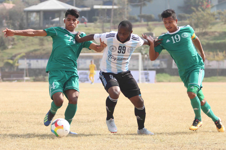Afeez Olawale Oladipo (center) of Manang Marsyangdi Club vies for the ball against Saroj Tamang (left) and skipper Dikesh Khadgi of New Road Team during their Pulsar Martyru2019s Memorial u2018Au2019 Division League match at APF Football Ground in Halchwok, Kathmandu on Saturday, November 17, 2018. Photo: THT