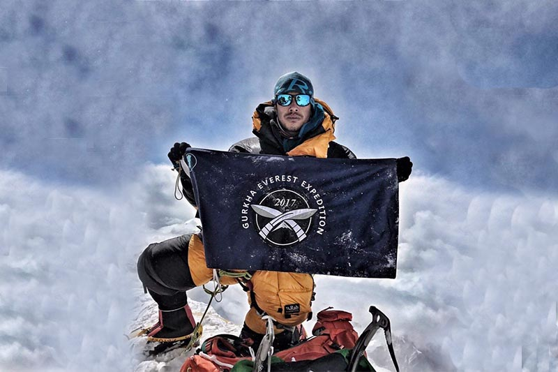 This image shows former Gurkha soldier Nirmal Purja holding a banner at the summit of Mount Everest, in 2017.