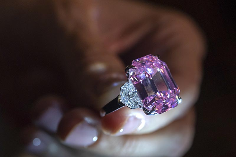 A Christie's employee displays an 18.96-carat fancy vivid pink diamond during a preview at Christie's in Geneva, Switzerland, on Thursday, November 8, 2018. Photo: Martial Trezzini/Keystone via AP