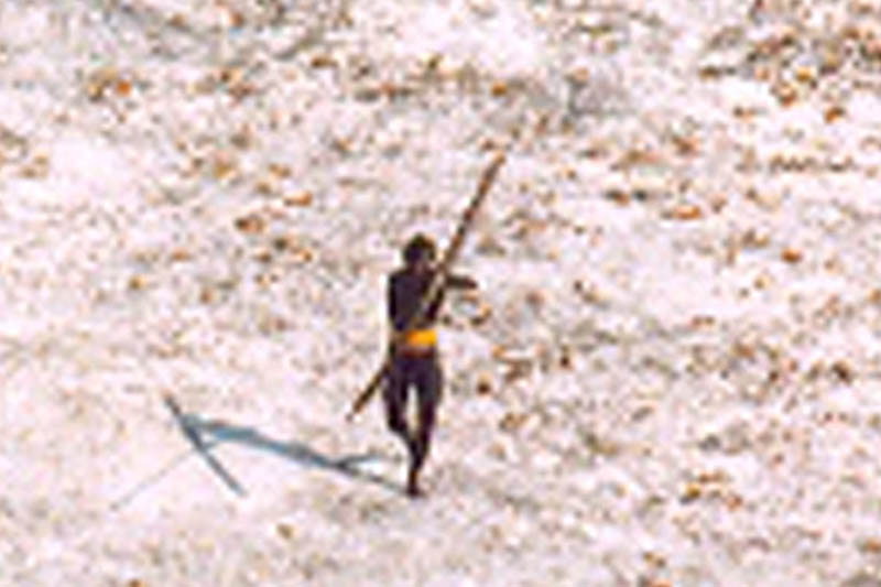 FILE PHOTO: A Sentinel tribal man aims with his bow and arrow at an Indian Coast Guard helicopter as it flies over the island for a survey of the damage caused by the tsunami in India's Andaman and Nicobar archipelago, December 28, 2004. Photo: Reuters