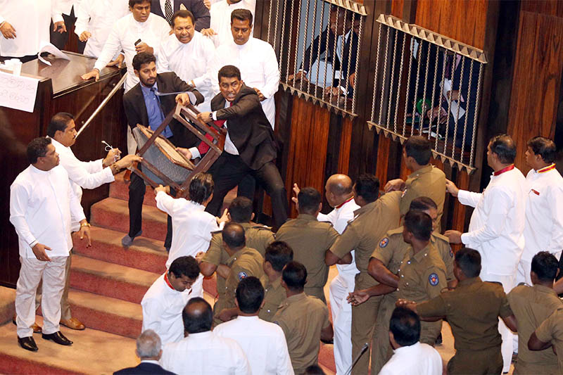 Parliament member Johnston Fernando who is backing newly appointed Prime Minister Mahinda Rajapaksa throws a chair at police who are there to protect parliament speaker Karu Jayasuriya (not pictured) during a parliament session in Colombo, Sri Lanka November 16, 2018. Photo: Reuters