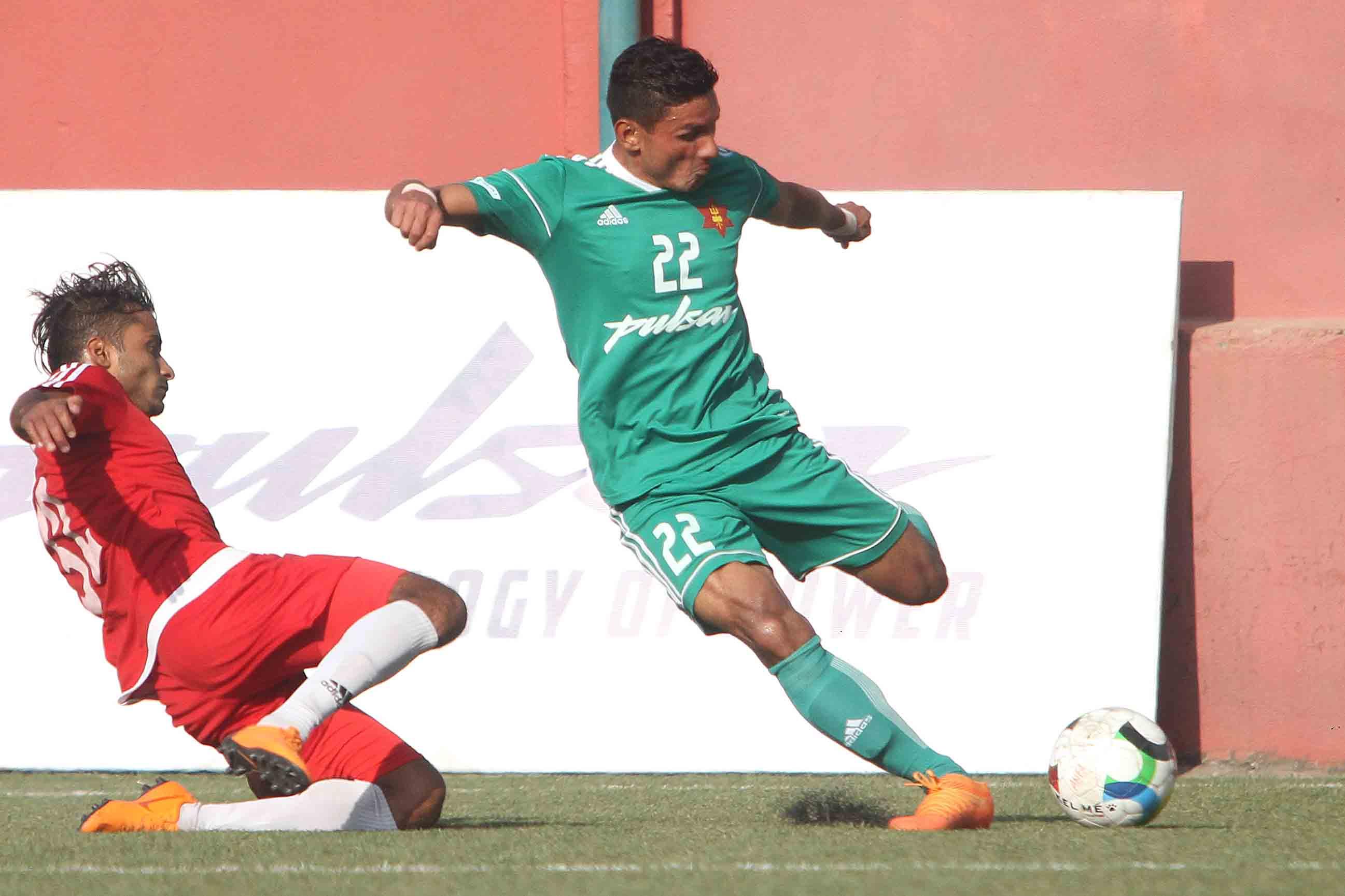 Tek Bahadur Budhathoki of TAC shoots the ball under pressure from Ajit Bhandari of NPC during their Pulsar Martyrs Memorial A Division League match in Lalitpur on Friday. Photo: THT