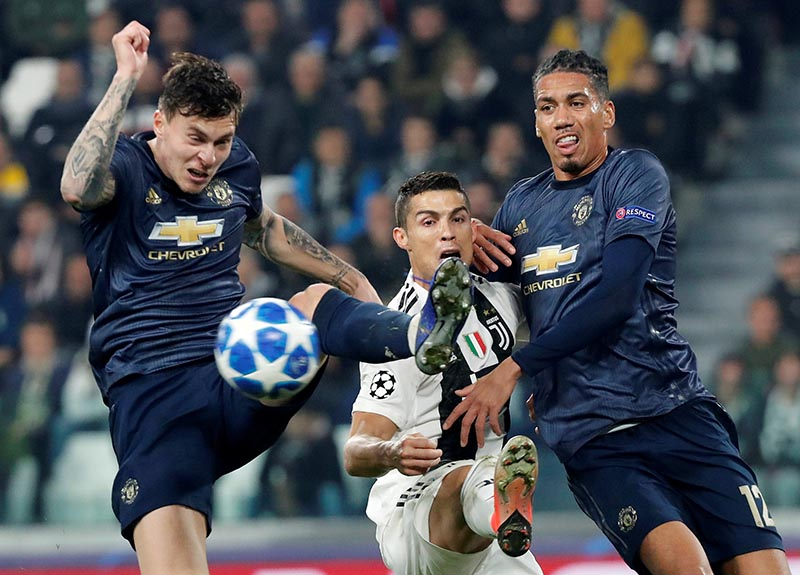 Juventus' Cristiano Ronaldo in action with Manchester United's Victor Lindelof and Chris Smalling during the Champions League  Group Stage match of Group H between Juventus and Manchester United, at Allianz Stadium, in Turin, Italy, on November 7, 2018. Photo: Reuters