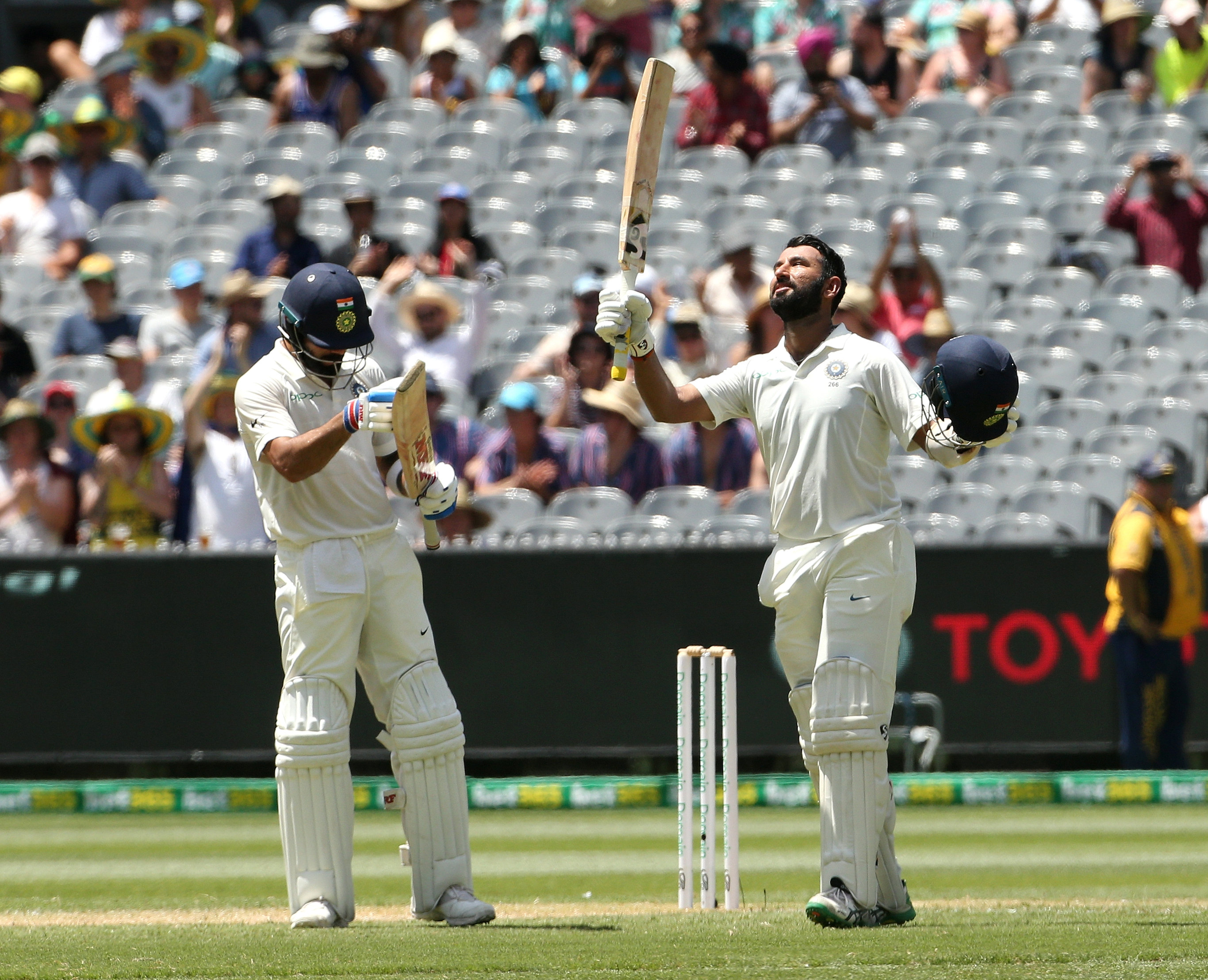 India's Cheteshwar Pujara (R) celebrates his century with captain Virat Kohli applauding on day two of the third test match between Australia and India at the MCG in Melbourne, Australia, December 27, 2018. Reuters