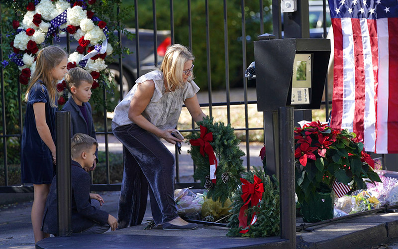 Tiffany Utterson, right, and her children, from left to right, Ella, 11, Ian, 10 and Owen, 8, place a wreath outside the gated community entrance to the home of George HW Bush, in Houston, on Sunday, Dec 2, 2018. Photo: AP