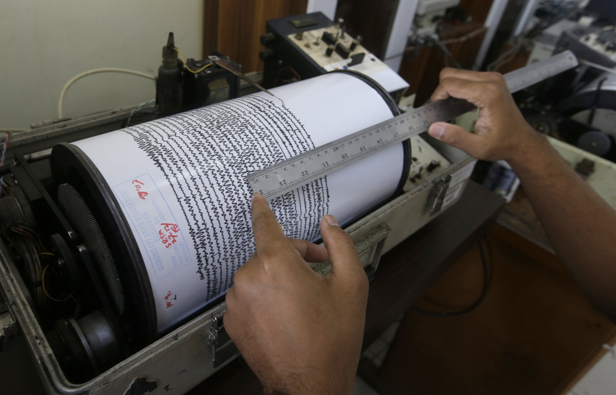 An official looks a seismograph at an observation post near a recent volcanic eruption in Carita, Indonesia, on Thursday, Dec. 27, 2018. Photo: AP