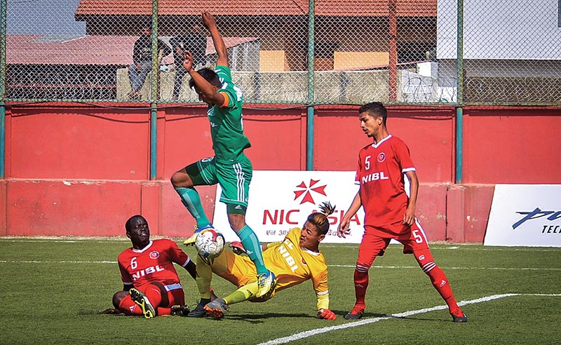 TAC stand-in skipper Nawayug Shrestha (centre) vies for the ball with NIBL Friends Club goalkeeper DevLimbu and two defenders during theiru00a0 Pulsar Martyrs Memorial A Division League match at the ANFA Complex grounds in Lalitpur on Thursday. Photo: Naresh Shrestha/ THT