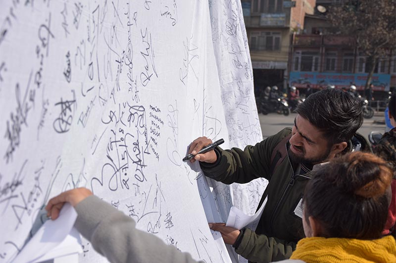 People signing on a banner during a signature campaign seeking justice for 13-year-old Nirmala Panta who was raped and murdered in Kanchanpur, at Maitighar, Kathmandu, on Monday, December 24, 2018. Photo: Naresh Krishna Shrestha/THT