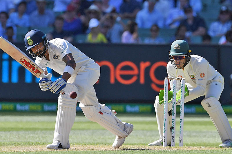 India's captain Virat Kohli (L) plays a shot watched by Australia's captain and wicketkeeper Tim Paine on day one of the third test match between Australia and India at the MCG in Melbourne, Australia, December 26, 2018. Photo: Reuters