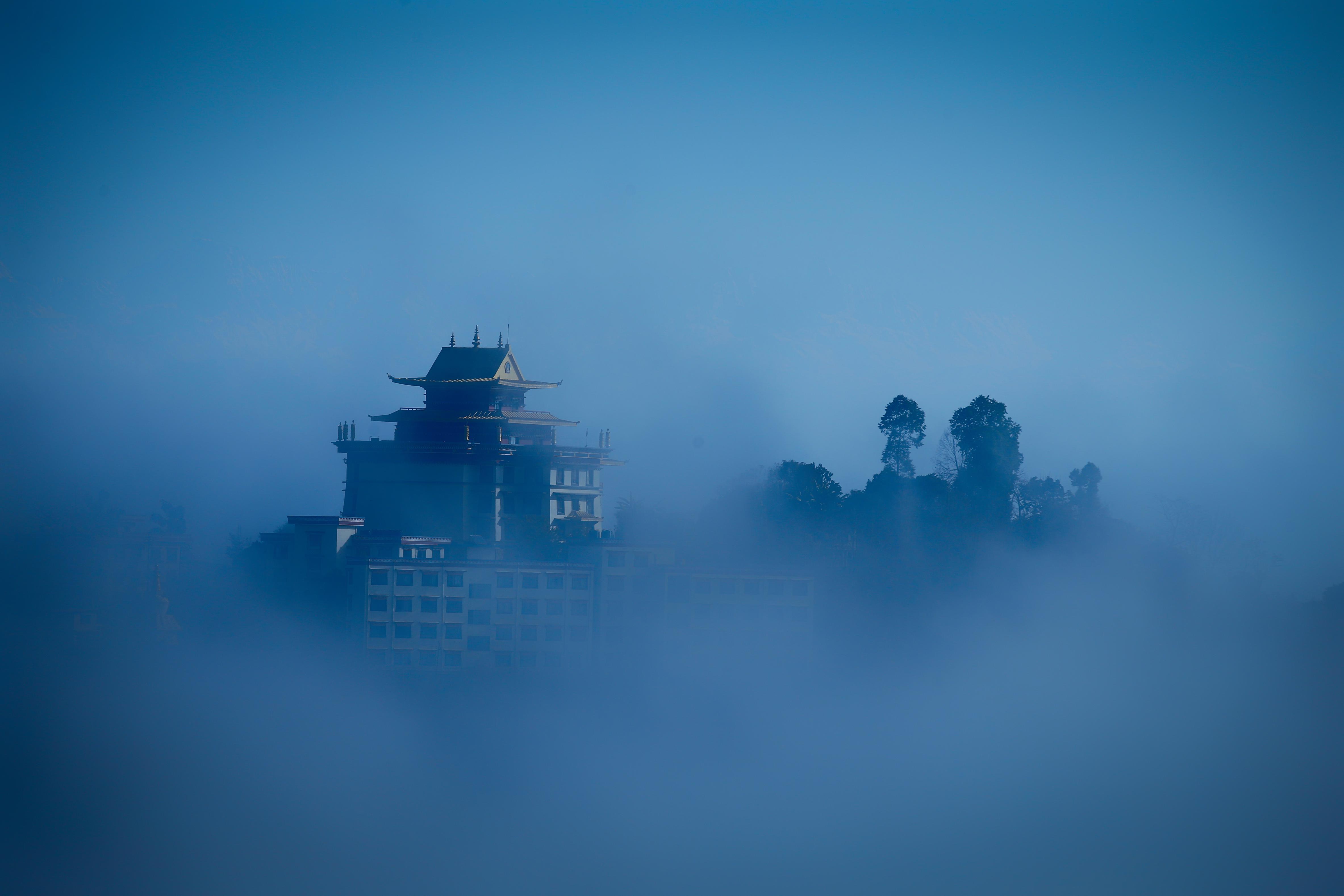 Fog engulfs a monastery seen from the heights of Pharping on the outskirts of Kathmandu, Nepal on Thursday, January 24, 2019. Photo: Skanda Gautam/THT