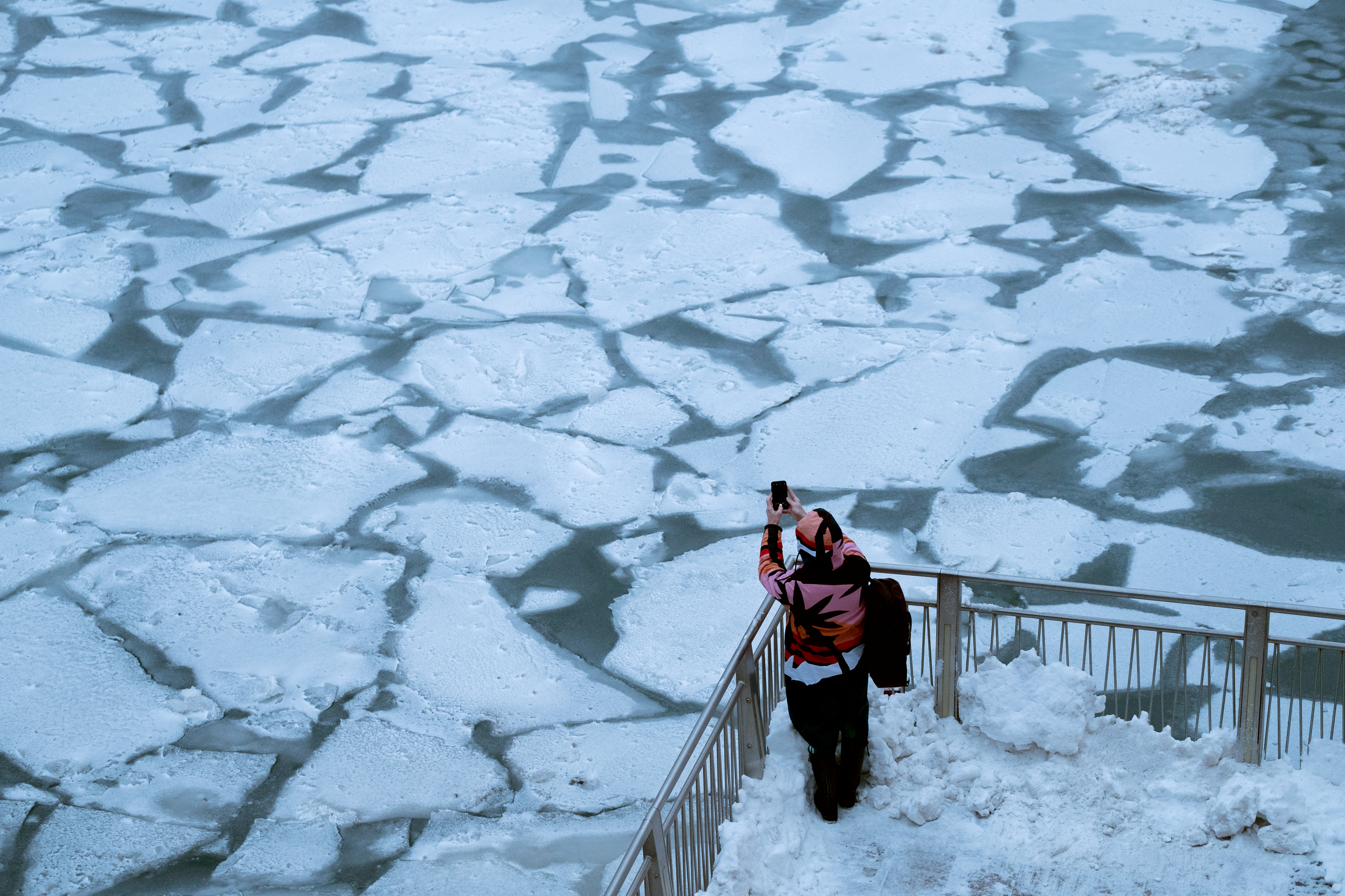 A pedestrian stops to take a photo by Chicago River, as bitter cold phenomenon called the polar vortex has descended on much of the central and eastern United States, in Chicago, Illinois, U.S., January 29, 2019.  REUTERS