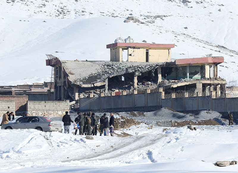 Afghan men stand in front of a collapsed building of a military base after a car bomb attack in Maidan Wardak, Afghanistan, January 21, 2019. Photo: Reuters