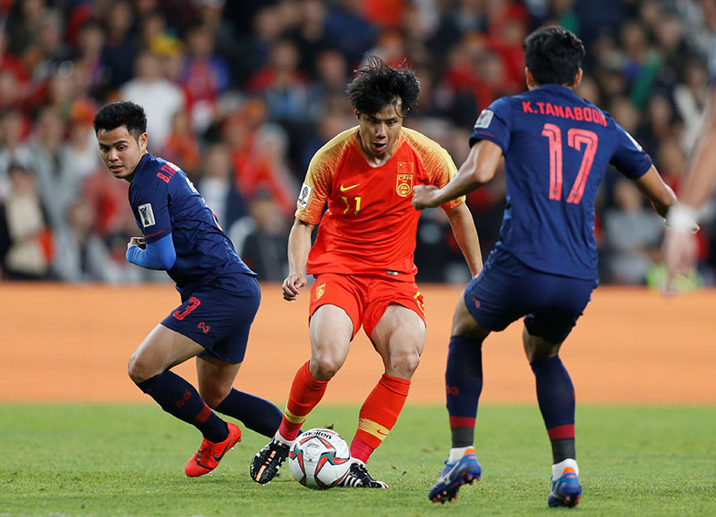 China's Hao Junmin in action with Thailand's Theerathon Bunmathan and Tanaboon Kesarat during the AFC Asian Cup Round of 16 match between Thailand and China, at Hazza Bin Zayed Stadium, Al Ain,in United Arab Emirates, onJanuary 20, 2019. Photo: Reuters
