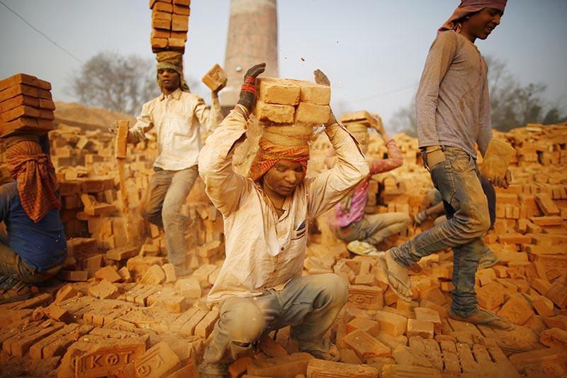 Indian migrant laborers carry stacked bricks on their head at a brick kiln in Bhaktapur, on Thursday, January 10, 2019. Photo: Skanda Gautam/THT
