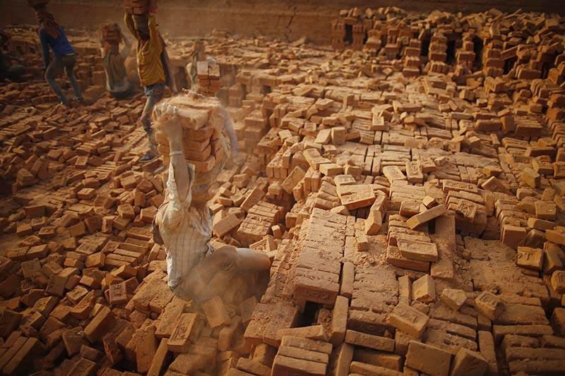Indian migrant labourers carry stacked bricks on their head at a brick kiln in Bhaktapur, on Thursday, January 10, 2019. Photo: Skanda Gautam/THT