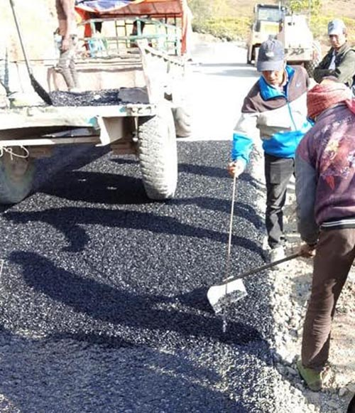 Workers blacktopping the Bhojpur-Khotang road section along the Pushpalal Mid-hilly Lokmarga in Bhojpur, on Tuesday, January 1, 2019. Photo: THT