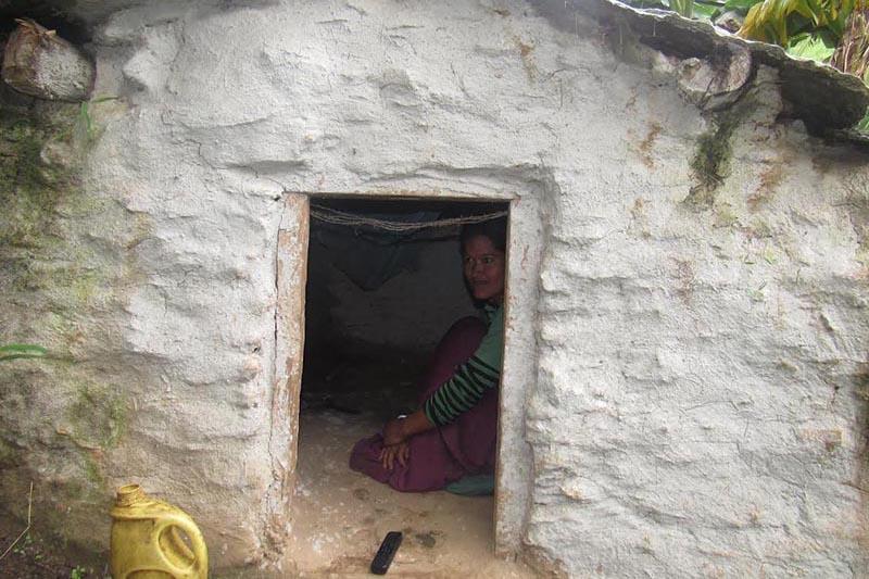 FILE - A menstruating woman sitting inside a chhaupadi shed in Budhinanda Municipality, Bajura, on Tuesday, January 8, 2019. Photo: THT